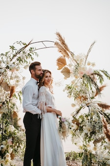 Mooie bruid en bruidegom die een strandhuwelijk hebben