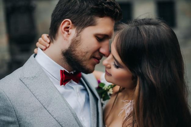 Mooie bruid en bruidegom die en op hun huwelijksdag in openlucht omhelzen kussen