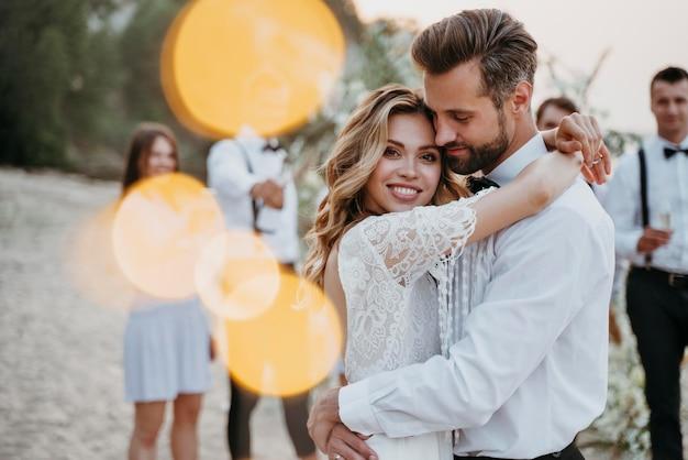 Mooie bruid en bruidegom die hun huwelijk met gasten op een strand hebben