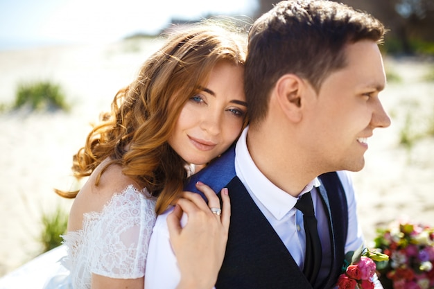 Mooie bruid en bruidegom genieten van elkaar wandelen langs het strand. gelukkig romantisch jong koppel viert hun huwelijk