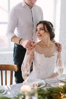 Mooie bruid en bruidegom in de buurt van bruiloft tafel met bruidstaart, blauwe kaarsen en grenen decoraties