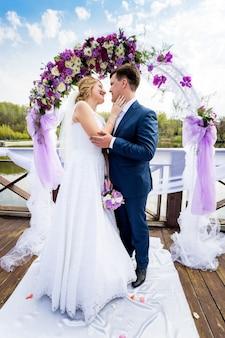 Mooie bruid en bruidegom knuffelen onder versierde bloemenboog