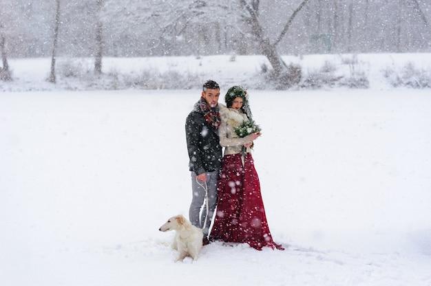 Mooie bruid en bruidegom met een witte hond staan op de achtergrond van een besneeuwde bos