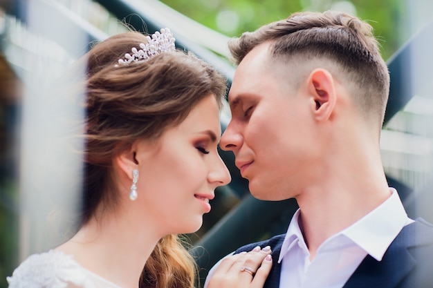 Mooie bruid en bruidegom omarmen en zoenen op hun trouwdag.
