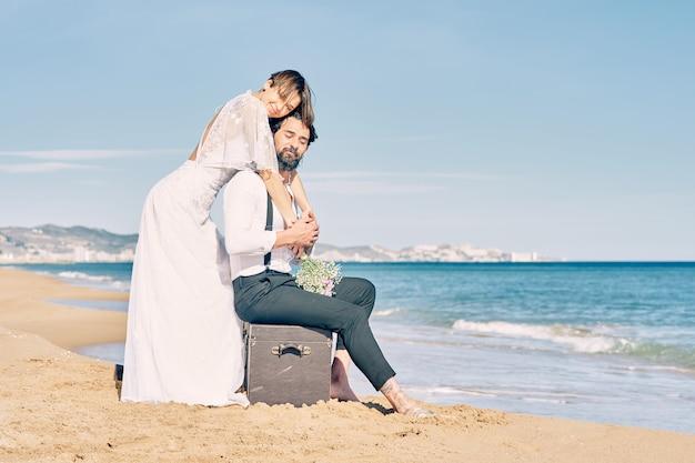 Mooie bruid en bruidegom op het strand omhelzen elkaar in trouwjurken