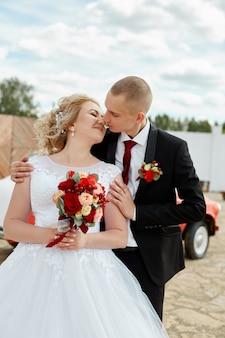 Mooie bruid en bruidegom poseren buitenshuis
