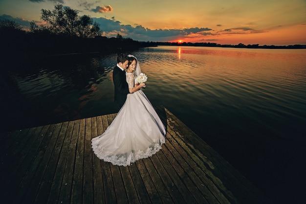 Mooie bruid en bruidegom poseren in de buurt van het meer bij zonsondergang
