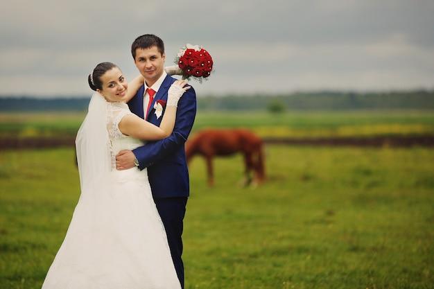 Mooie bruid en bruidegom poseren in de natuur