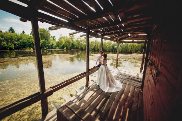 Mooie bruid en bruidegom poseren op een brug