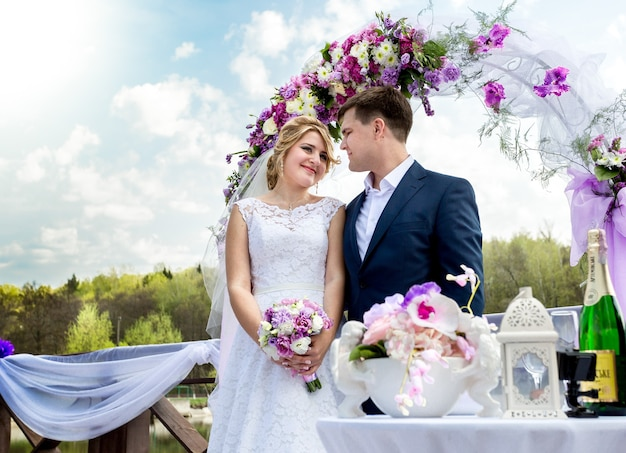 Mooie bruid en bruidegom staan onder bloemenboog op zonnige dag
