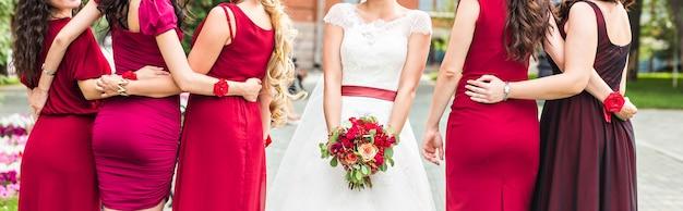Mooie bruid en bruidsmeisjes poseren buiten in het park
