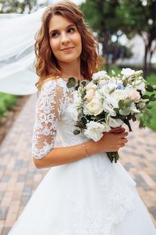 Mooie bruid in de natuur, portret van een meisje in een witte jurk