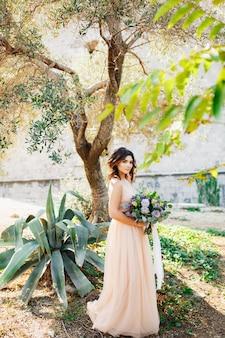 Mooie bruid in een beige jurk staat tegen een boom met een prachtig boeket bloemen
