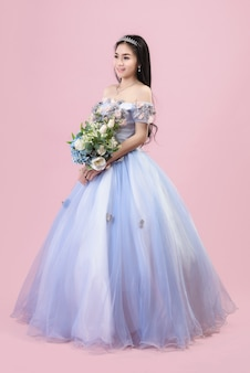 Mooie bruid in een fantasie trouwjurk op een roze achtergrond in de studio.