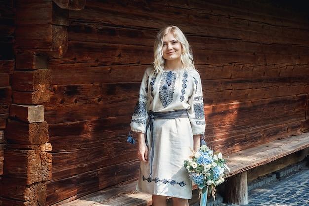 Mooie bruid in een geborduurd shirt met een bos bloemen op de achtergrond van een houten huis.