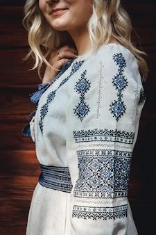 Mooie bruid in een geborduurd shirt op de achtergrond van een houten huis. patroondetails.