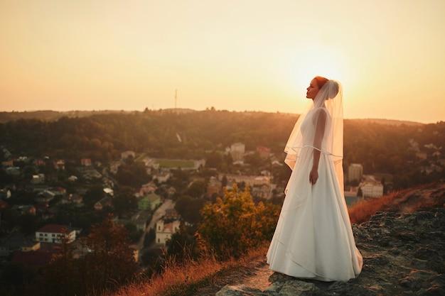Mooie bruid in een lange bruidssluier bij zonsondergang buiten de stad
