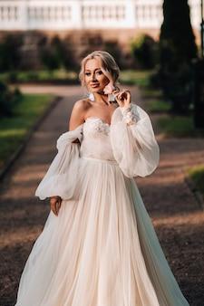 Mooie bruid in een luxe trouwjurk heeft een boeket witte rozen en groenen op een groene natuurlijke achtergrond. portret van gelukkige bruid in witte jurk glimlachend op muur achtergrond met groenen.