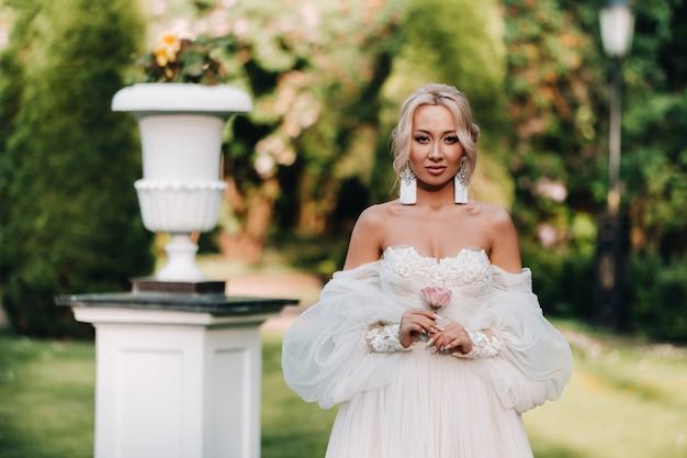Mooie bruid in een luxe trouwjurk houdt een boeket witte rozen en groenen op een groene natuurlijke achtergrond. portret van gelukkige bruid in witte jurk glimlachend op muur achtergrond met groenen.