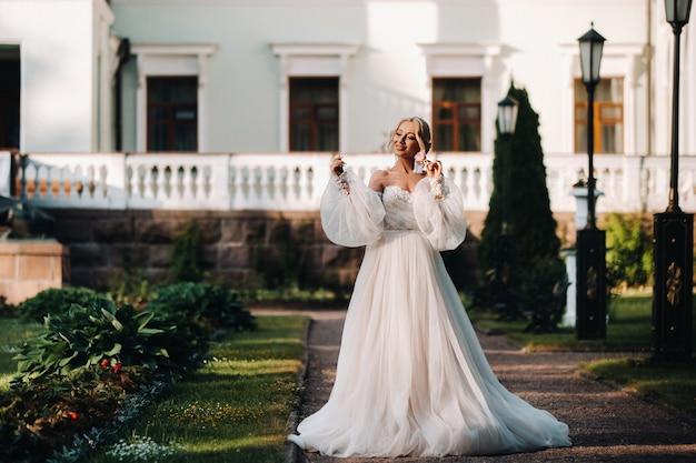 Mooie bruid in een luxe trouwjurk op een groene natuurlijke achtergrond