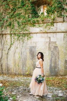 Mooie bruid in een pastelkleurige jurk loopt met een luxe boeket bloemen aan de muur