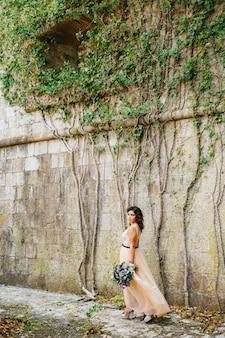 Mooie bruid in een pastelkleurige jurk loopt met een luxe boeket bloemen langs de stenen muur