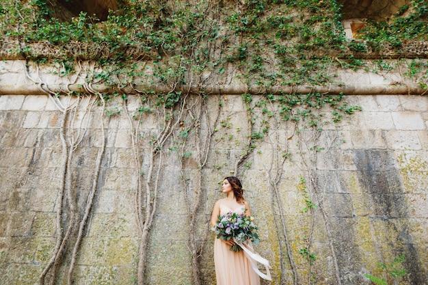 Mooie bruid in een pastelkleurige jurk met een luxe boeket bloemen