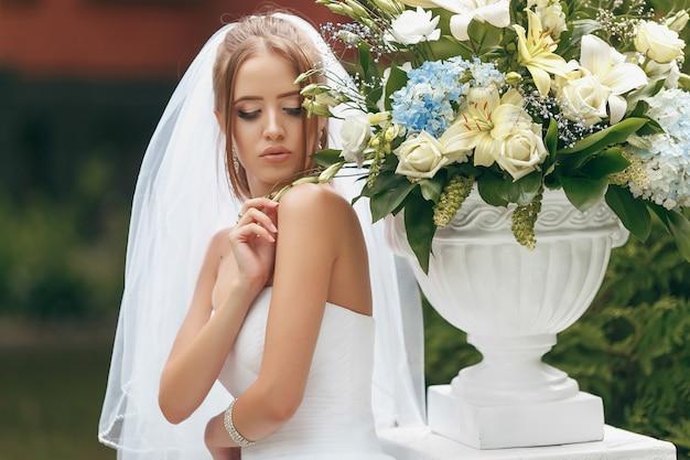 Mooie bruid in een prachtige trouwjurk poseren tussen groen op straat. bruidconcept voor reclamekleding