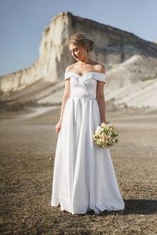 Mooie bruid in een trouwjurk met een boeket dat zich tegen witte rots bevindt