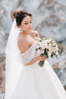 Mooie bruid in een trouwjurk met een boeket op de top van de zoutbergen. een prachtige jonge bruid met krullend haar.