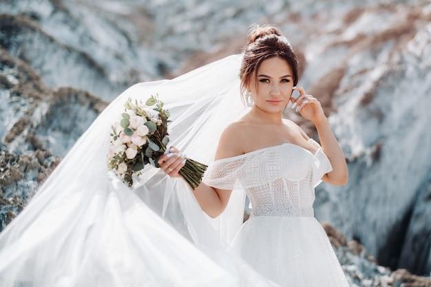 Mooie bruid in een trouwjurk met een boeket op de top van de zoutbergen