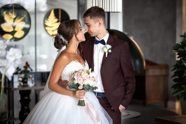 Mooie bruid in een witte jurk en een knappe bruidegom in een bordeauxrode pak kijken elkaar aan