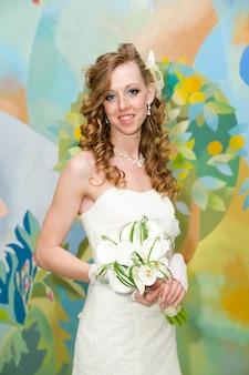 Mooie bruid in een witte jurk met een boeket calla lelies