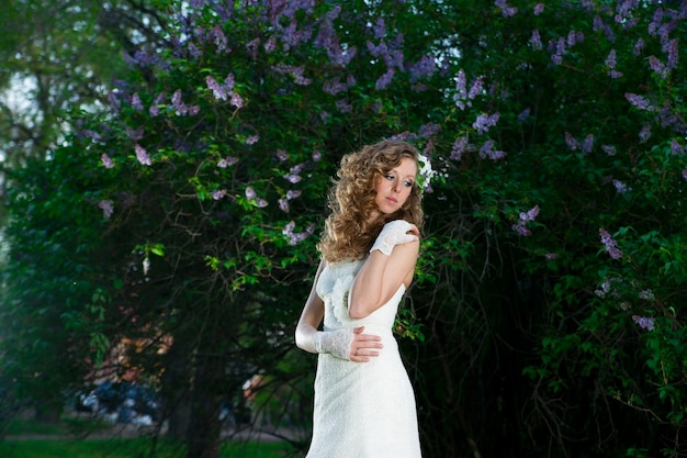 Mooie bruid in een witte jurk op een lila achtergrond in het voorjaar professionele make-up en haarstijl