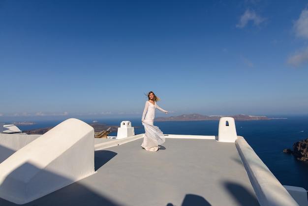 Mooie bruid in een witte jurk poseren op het dak van het huis tegen de achtergrond van de middellandse zee in thira, santorini.