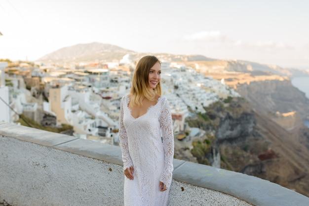 Mooie bruid in een witte jurk poseren tegen de achtergrond van de stad thira, santorini.