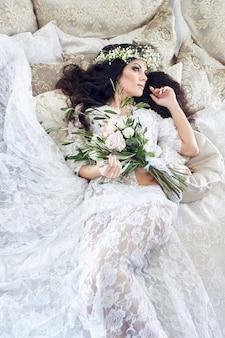 Mooie bruid in lingerie en met een krans van bloemen op haar hoofd, in de ochtend voor de bruiloft.