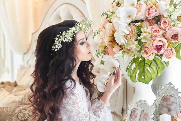 Mooie bruid in lingerie en met een krans van bloemen op haar hoofd