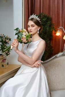 Mooie bruid in lond jurk zit op de bank bij het raam