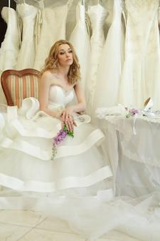 Mooie bruid in luxe interieur op achtergrond van trouwjurken, vintage glamour stijl