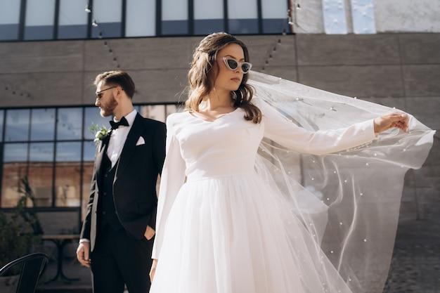 Mooie bruid in modieuze zonnebril en witte jurk staat voor een knappe bruidegom