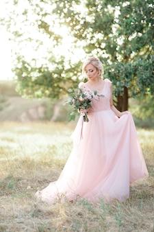 Mooie bruid in roze jurk met boeket bloemen in de natuur. fijne kunstfotografie.