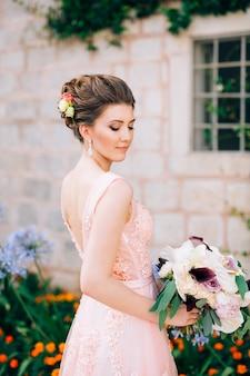 Mooie bruid in tedere trouwjurk met bruidsboeket in perast.