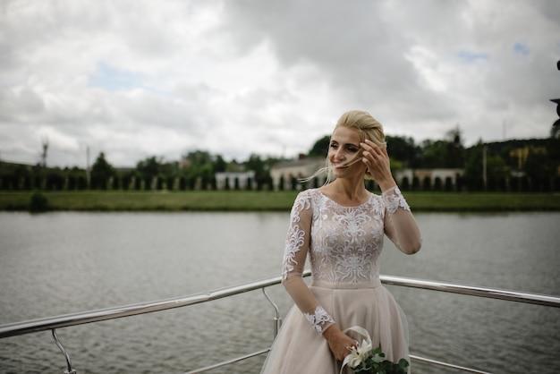 Mooie bruid in trouwjurk aan het meer