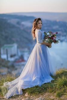 Mooie bruid in trouwjurk op de bergtop. prachtige jonge bruid met krullend haar en een boeket bloemen in haar handen. trouwdag. .mooi portret van een bruid zonder bruidegom