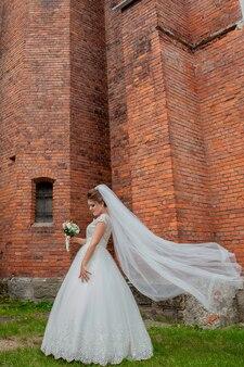 Mooie bruid in trouwjurk poseren in de buurt van de bakstenen muur