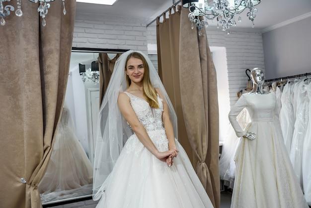 Mooie bruid in trouwjurk staande in boutique