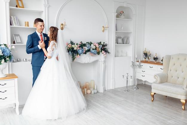 Mooie bruid in witte jurk en bruidegom in pak, poseren in witte studio interieur, bruiloft