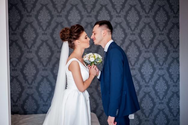 Mooie bruid in witte jurk met boeket van bruiden en knappe bruidegom in blauw pak permanent thuis thuis
