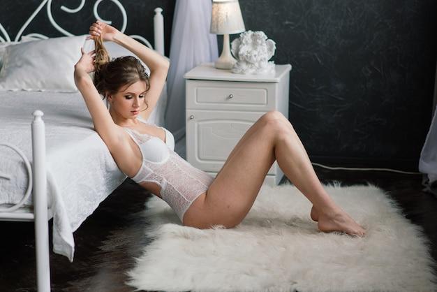 Mooie bruid in witte kanten lingerie, met blote schouder zittend in een hotelkamer